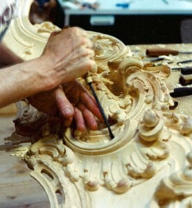 A woodcarver for Agrell Architectural Carving uses hand tools to shape a Rococo-style fireplace.