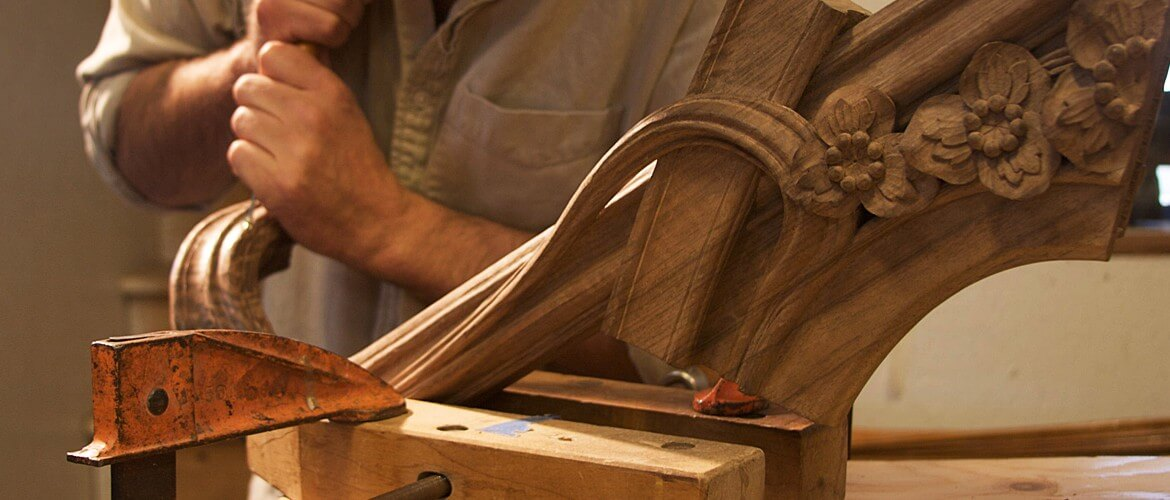 A woodcarver for Agrell Architectural Carving works on a component for an Art Nouveau-style bed.