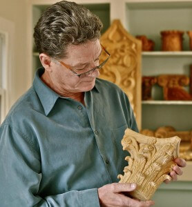 Ian Agrell holds a Corinthian capital hand-carved by Agrell Architectural Carving.