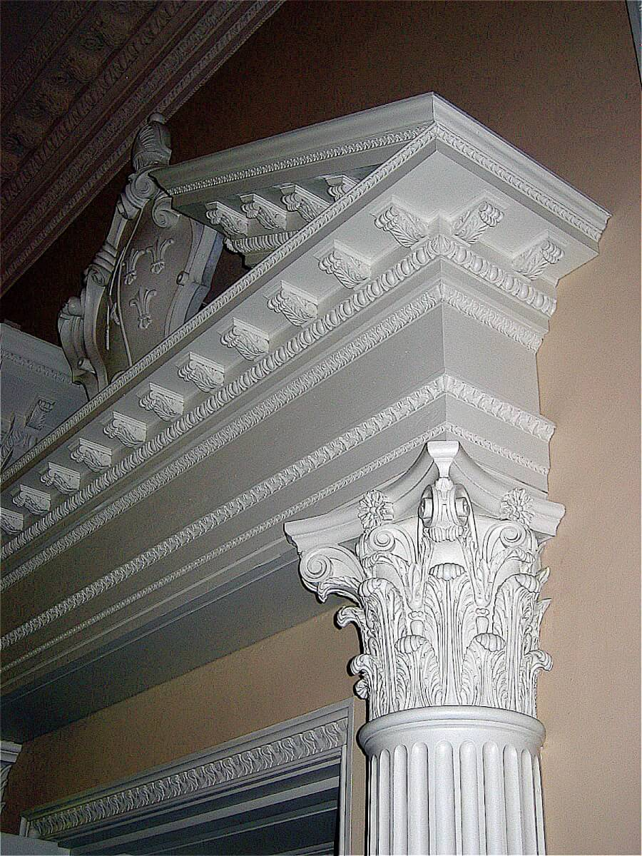 Door surround with Corinthian capitals, dentil blocks, and a split pediment