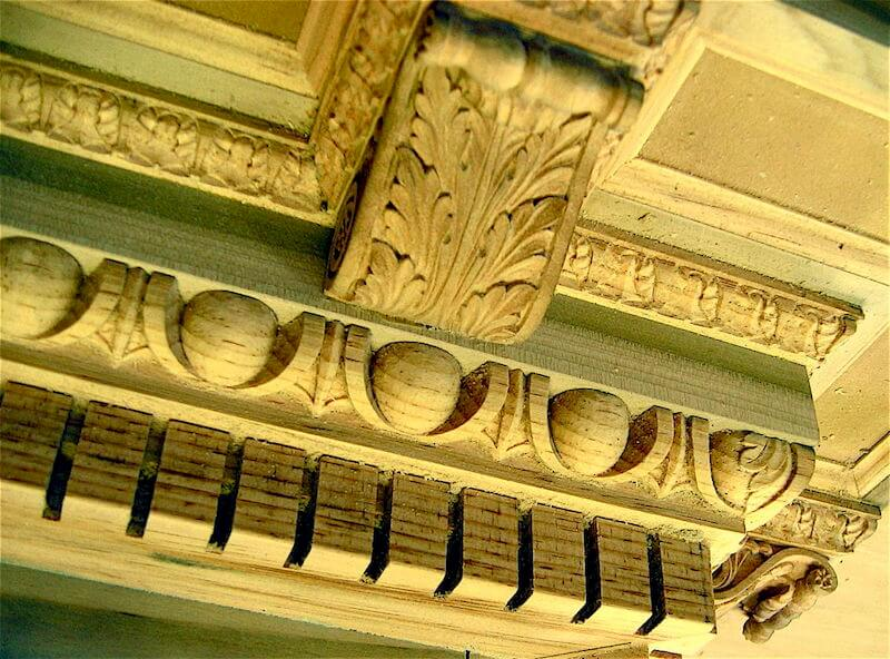 Hand-carved mouldings installed on a wood entablature. By Agrell Architectural Carving.