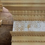 Roman-style entablature with woodcarvings by Agrell Architectural Carving. Features lamb's tongue, egg and dart, bead and reel, and an elaborate frieze.