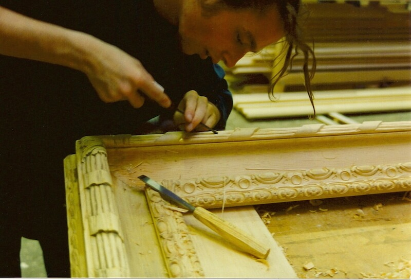 A woodcarver uses hand tools to carve ribbon and reed moulding in wood.