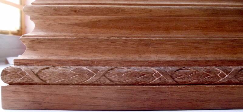 Wood-carved laurel leaf moulding installed on a column base. By Agrell Architectural Carving.