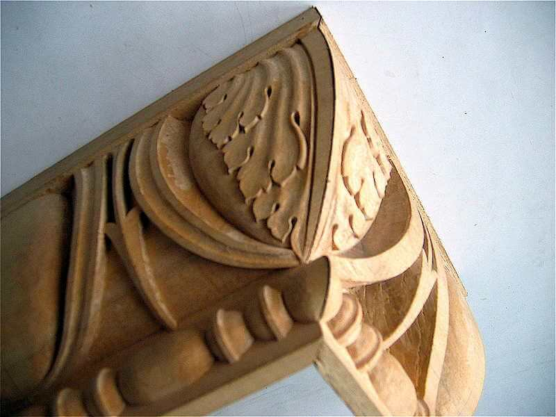 To avoid a messy clash of shapes, we typically carve an acanthus motif on the miters of our mouldings. Doing so also retains the profile of the moulding along the miter.