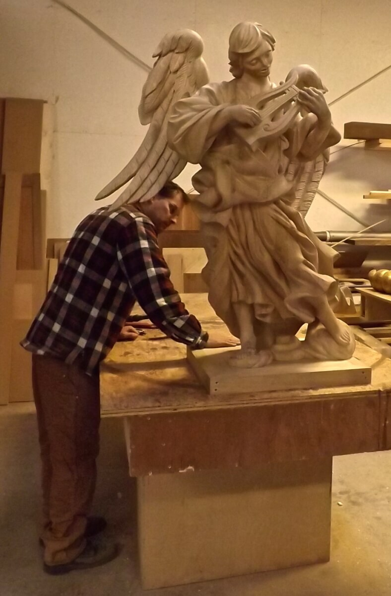A woodcarver works on an angel for the Cathedral of St. Paul, Minn.