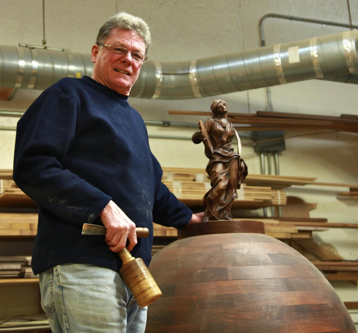 Ian Agrell poses with a hand-carved model of St. Cecilia