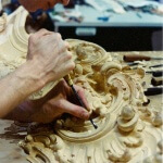 A woodcarver for Agrell Architectural Carving works on an English Rococo fireplace