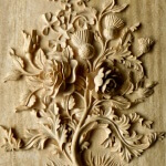 Carved wood panel featuring roses, thistles, and shamrocks